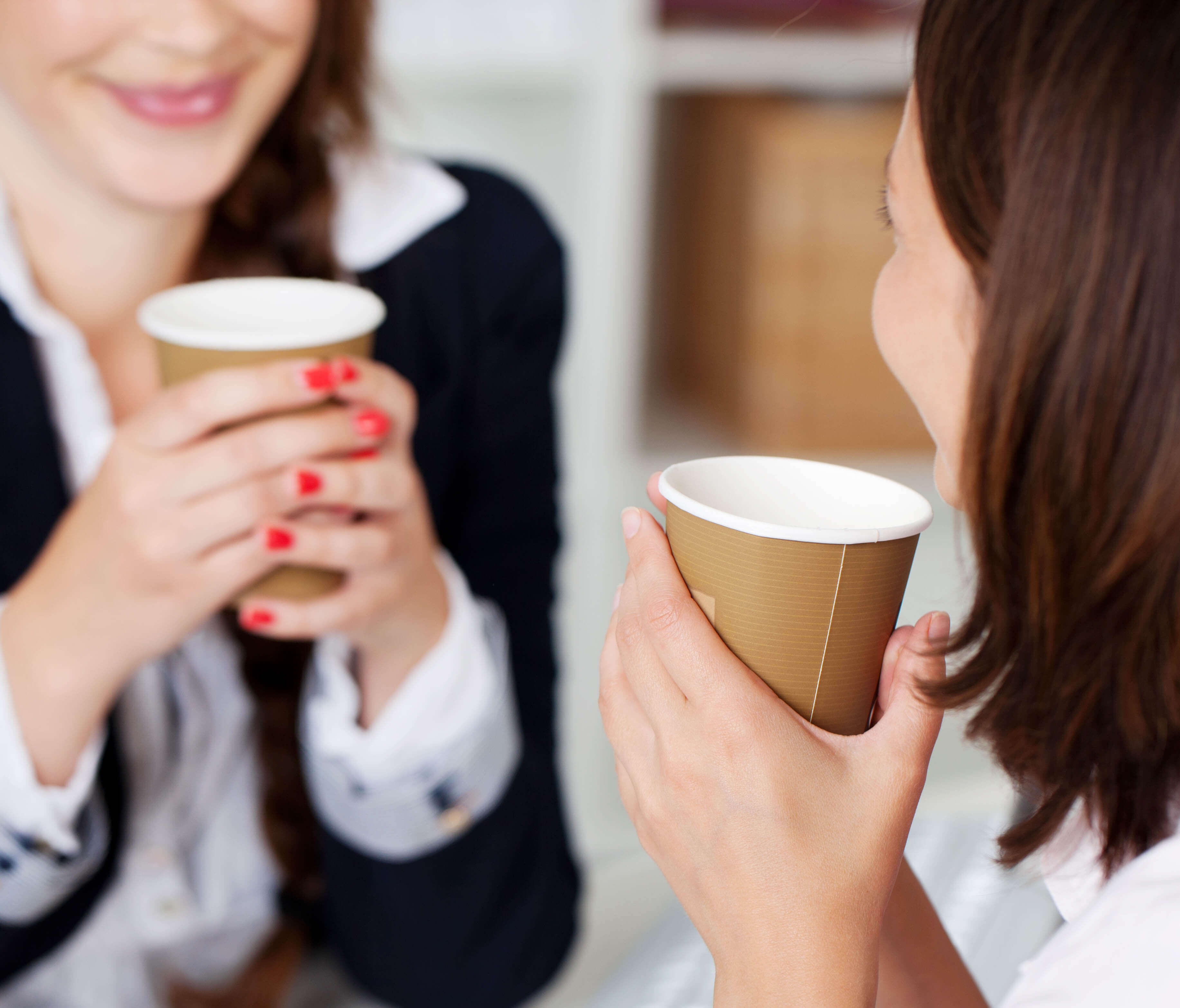 Due colleghe sorridenti in Pausa Caffé